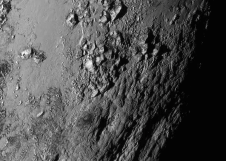 New close-up images of a region near Pluto's equator reveal a giant surprise — a range of youthful mountains rising as high as 11,000 feet (3,500 meters) above the surface of the icy body. Credits: NASA/JHU APL/SwRI