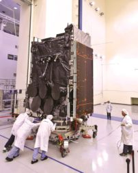 Boeing technicians push the WGS-5 satellite into an acoustic test chamber. Credit: Boeing