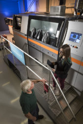 Engineers and researchers stand near one of the two metal laser-deposition machines at Lockheed Martin's Additive Design and Manufacturing Center. Credit: Lockheed Martin